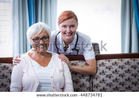 Portrait of smiling doctor and patient at home - stock photo