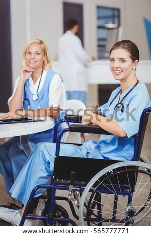 Portrait of smiling doctor sitting on wheelchair with colleagues in hospital