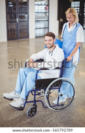 Portrait of smiling doctor sitting on wheelchair with female colleague at hospital
