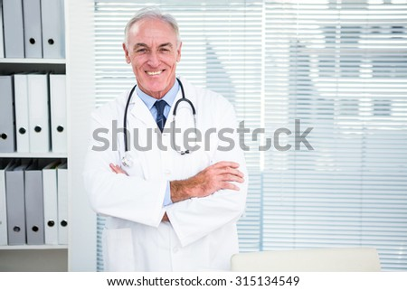 Portrait of smiling doctor with stethoscope around his neck at clinic - stock photo