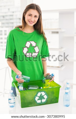 Portrait of smiling eco-minded brunette holding recycling bottles in the office