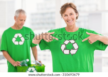 Portrait of smiling eco-minded woman showing her recycling shirt in the office