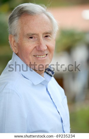 Portrait of smiling elderly man - stock photo