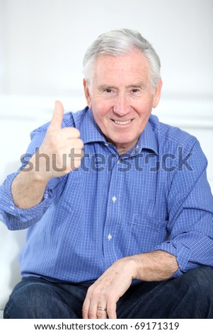 Portrait of smiling elderly man with thumb up - stock photo