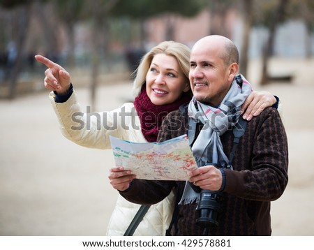 Portrait of smiling elderly spouses with paper map outdoors - stock photo