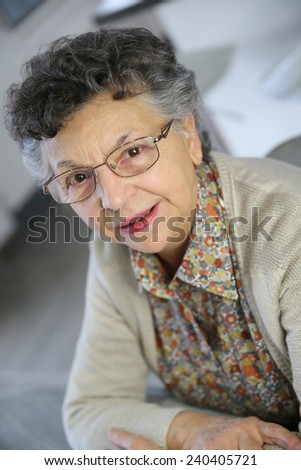 Portrait of smiling elderly woman with eyeglasses - stock photo