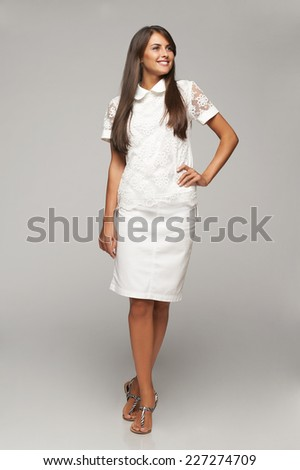 Portrait of smiling elegant business woman walking in full length looking away over gray background - stock photo