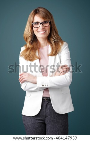 Portrait of smiling executive businesswoman with arms crossed standing at isolated background.