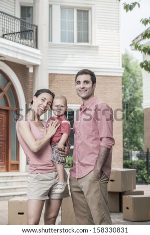 Portrait of smiling family in front of their new home - stock photo