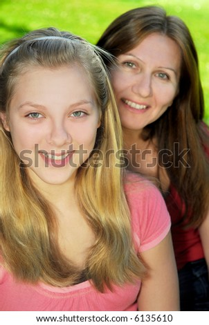 Portrait of smiling family of mother and her teenage daughter - stock photo