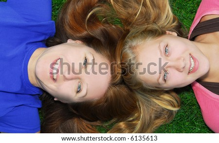 Portrait of smiling family of mother and her teenage daughter lying on grass in summer park - stock photo
