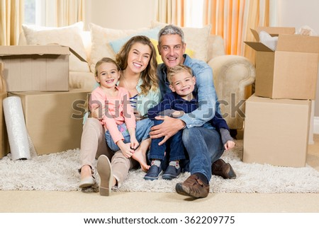 Portrait of smiling family sitting on the carpet in the living room - stock photo