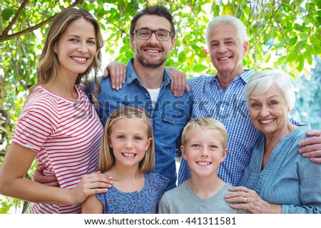 Portrait of smiling family standing against tree