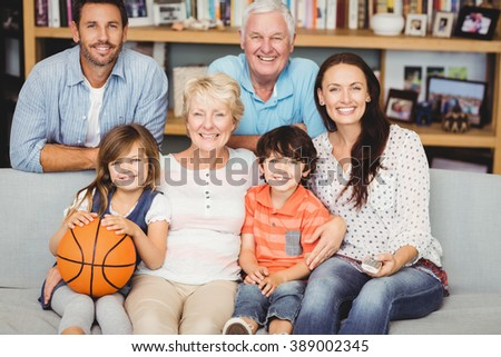 Portrait of smiling family watching basketball match at home - stock photo