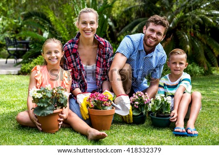 Portrait of smiling family with flower pots on grass at yard