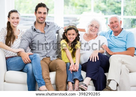 Portrait of smiling family with grandparents on sofa at home - stock photo