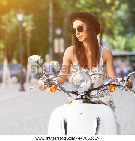 Portrait of smiling fashion girl riding a retro scooter on city streets wearing summer clothes and sunglasses - stock photo