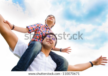Portrait of smiling father giving his son piggyback ride outdoors against sky - stock photo