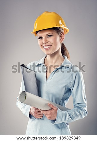 Portrait of smiling female architect holding blueprints and black folder. Young successful business woman carrying out construction project.  - stock photo