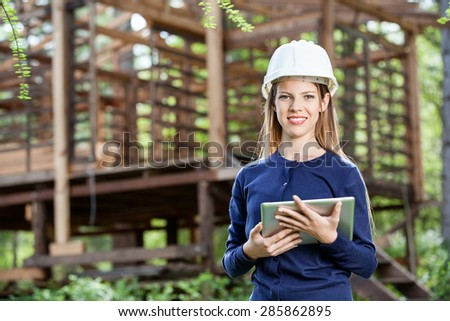 Portrait of smiling female architect holding digital tablet against incomplete timber cabin at construction site - stock photo