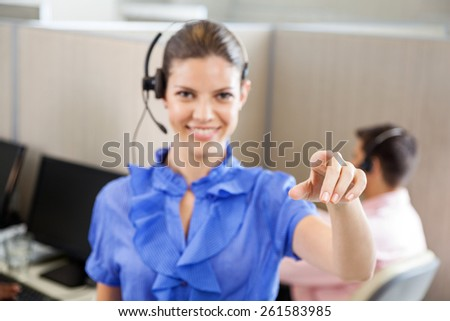 Portrait of smiling female call center employee pointing while colleague working in background at office - stock photo