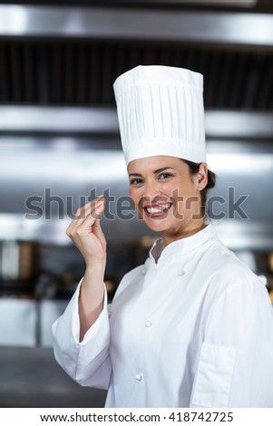 Portrait of smiling female chef gesturing in commercial kitchen - stock photo