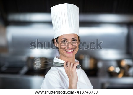 Portrait of smiling female chef holding wire whisk in commercial kitchen - stock photo