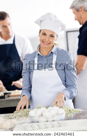 Portrait of smiling female chef preparing pasta at counter with colleagues in background at commercial kitchen - stock photo
