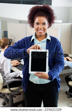 Portrait of smiling female customer service executive holding tablet computer while colleague working in background at call center - stock photo