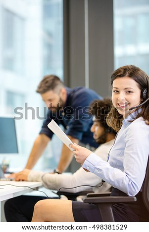 Portrait of smiling female customer service representative holding documents with colleagues in background at office