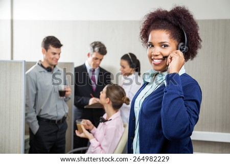 Portrait of smiling female customer service representative holding headphones while manager discussing with employees in background at call center - stock photo