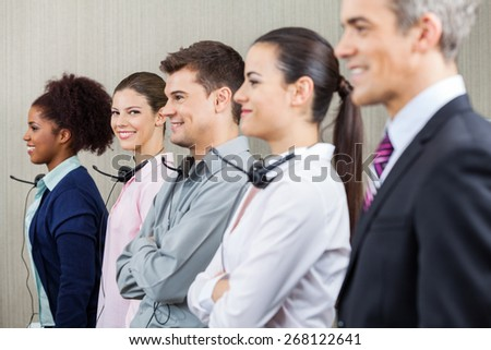 Portrait of smiling female customer service representative standing with colleagues and manager at call center - stock photo