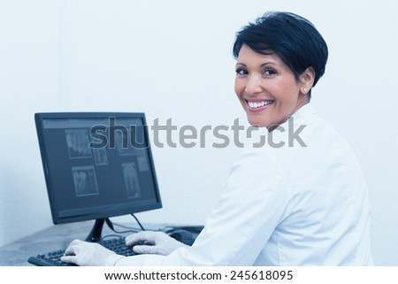 Portrait of smiling female dentist with x-ray on computer