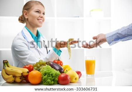 Portrait of smiling female dietitian giving measuring tape to patient. Slimming concept. - stock photo