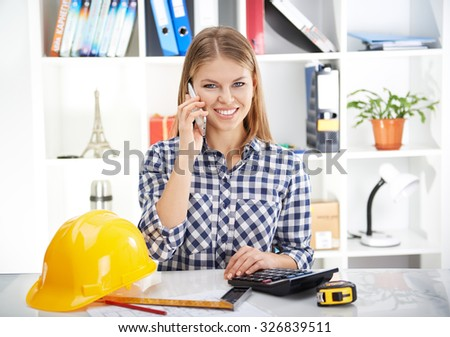 Portrait of smiling female engineer talking with customer on phone at her workplace. Young successful woman sitting at the desk with building instruments and yellow helmet.  - stock photo