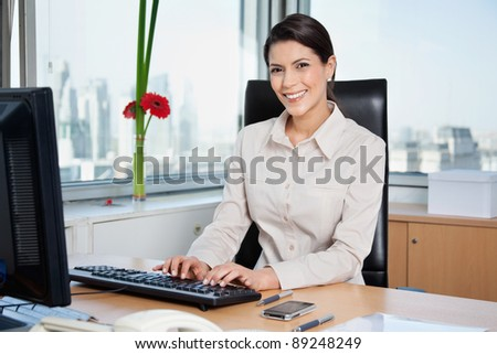 Portrait of smiling female entrepreneur working on computer in office - stock photo