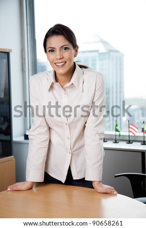 Portrait of smiling female executive standing near desk in office - stock photo