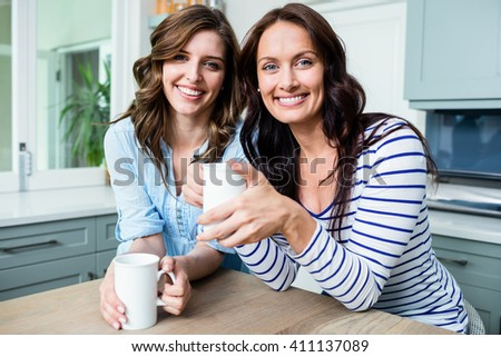 Portrait of smiling female friends holding coffee mugs while sitting at table in kitchen - stock photo