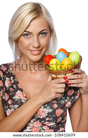 Portrait of smiling female holding basket with Easter eggs, isolated on white background