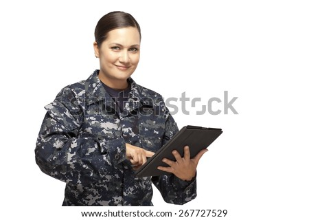 Portrait of smiling female navy sailor with digital tablet against white background - stock photo