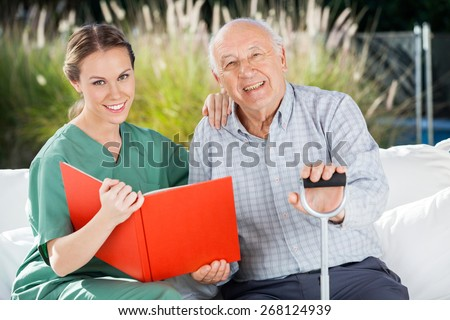 Portrait of smiling female nurse and senior man with book at nursing home - stock photo