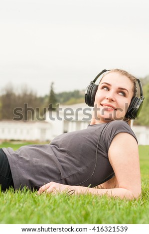 Portrait of smiling female on sunny summer day listening music and sitting on green grass - stock photo