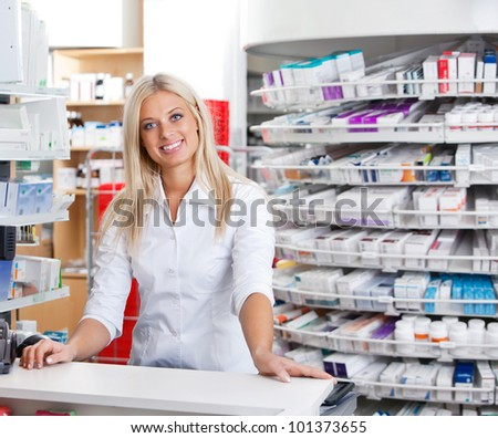 Portrait of smiling female pharmacist standing at checkout counter - stock photo