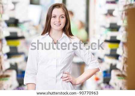Portrait of smiling female pharmacist standing with hand on hip - stock photo