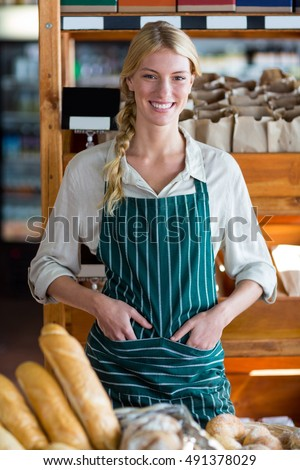Portrait of smiling female staff standing at bread counter in supermarket