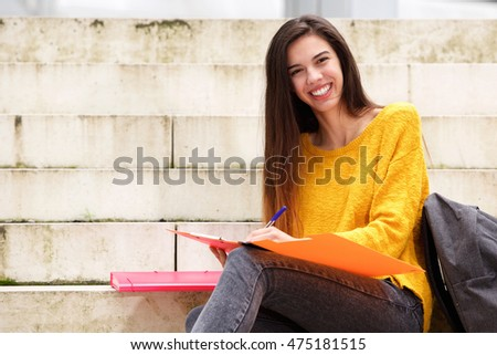 Portrait of smiling female student with notebook and pen