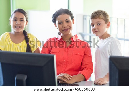 Portrait of smiling female teacher with children in computer class - stock photo