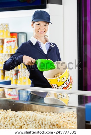 Portrait of smiling female worker pouring popcorn in bucket at cinema concession stand - stock photo
