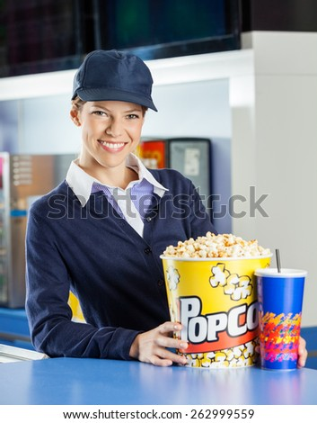 Portrait of smiling female worker with popcorn and drink at concession stand in cinema - stock photo