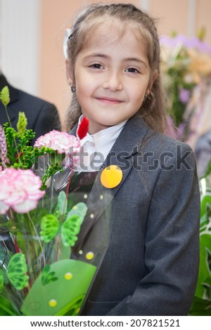 Portrait of smiling firs grade pupil with flowers in hands - stock photo